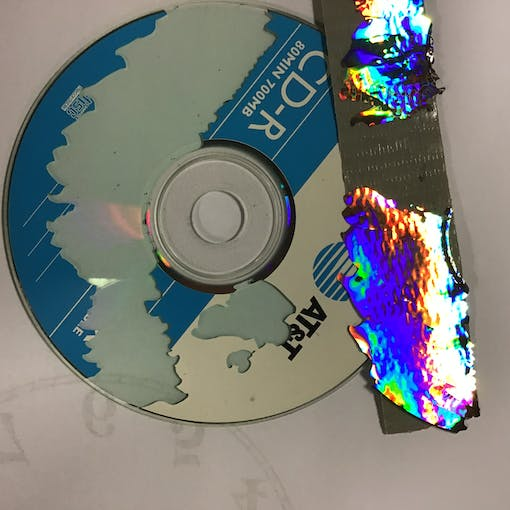 Removing silver coating from CD with tape.