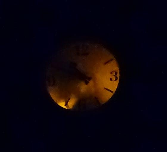 Clock at night illuminated by yellow LED stripes.
