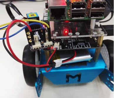 Place the battery in the space below the robot
