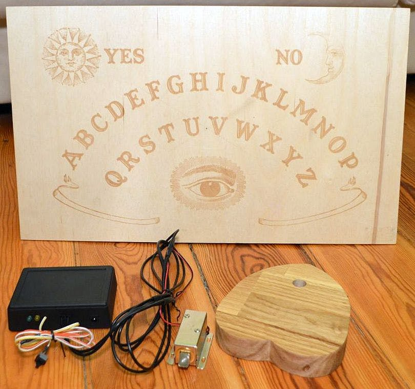 The complete system: the receiver, with an electronic lock and (not pictured) wires for charging the planchette, and the planchette itself. On the back of the board the RFID tags are placed.