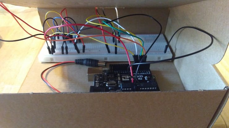 My breadboard and Arduino in their cardboard enclosure/servo motor trap assembly stand