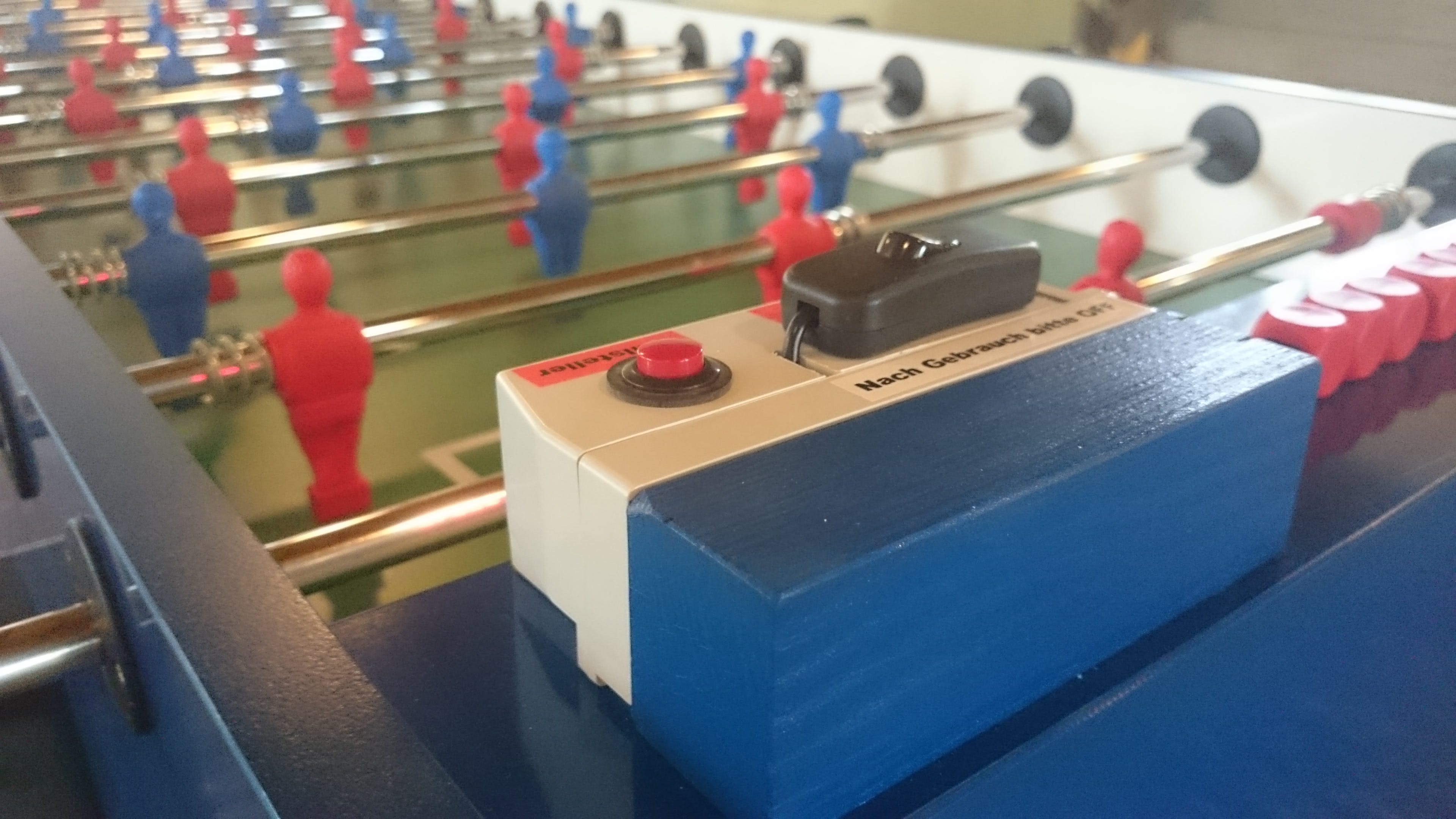 The display housing is mounted on the blue piece of wood, which is screwed onto the table.
