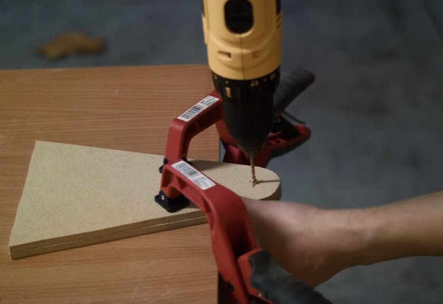 "Drill the holes into the leg. One 1/2"" hole on one leg. Four 1/8"" holes centered around a 5/8"" hole on the other leg"
