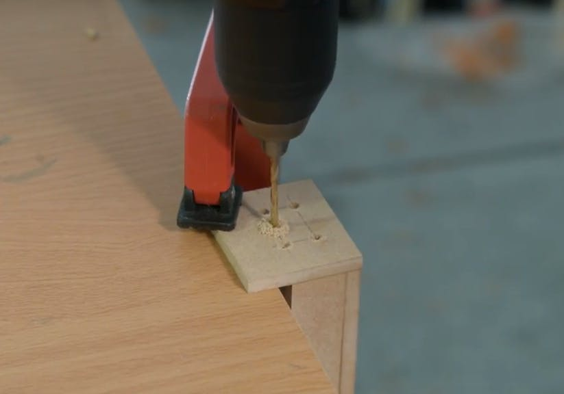 Drill a pilot hole in the center of the top mounting holes