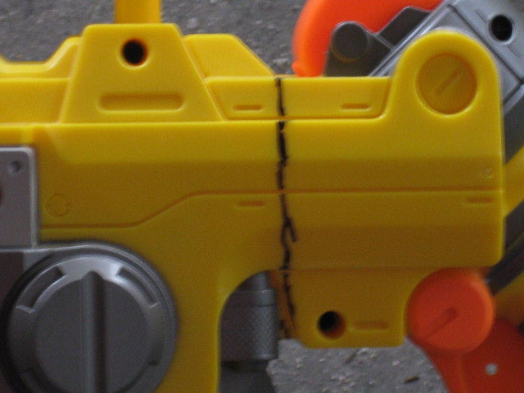 In order to do this mod, you must open up Nerf Vulcan. It would be a pain to open up the whole gun, so you need to make just one cut. This will allow you to open up just specific region of the gun. Begin by marking the region of the gun you are going to cut. (See second picture) Then use what ever method you would like to cut along the line to the spot where both sides of the gun meet. There are many methods of doing this. I just used a saw. Choose you method of cutting, and slice it down the line.