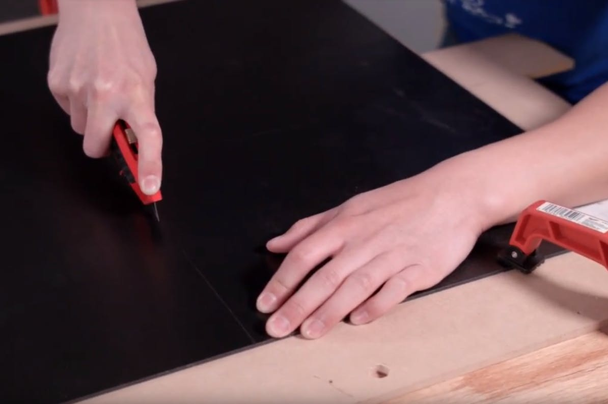 Cutting the PVC sheets with a box cutter to create the panels