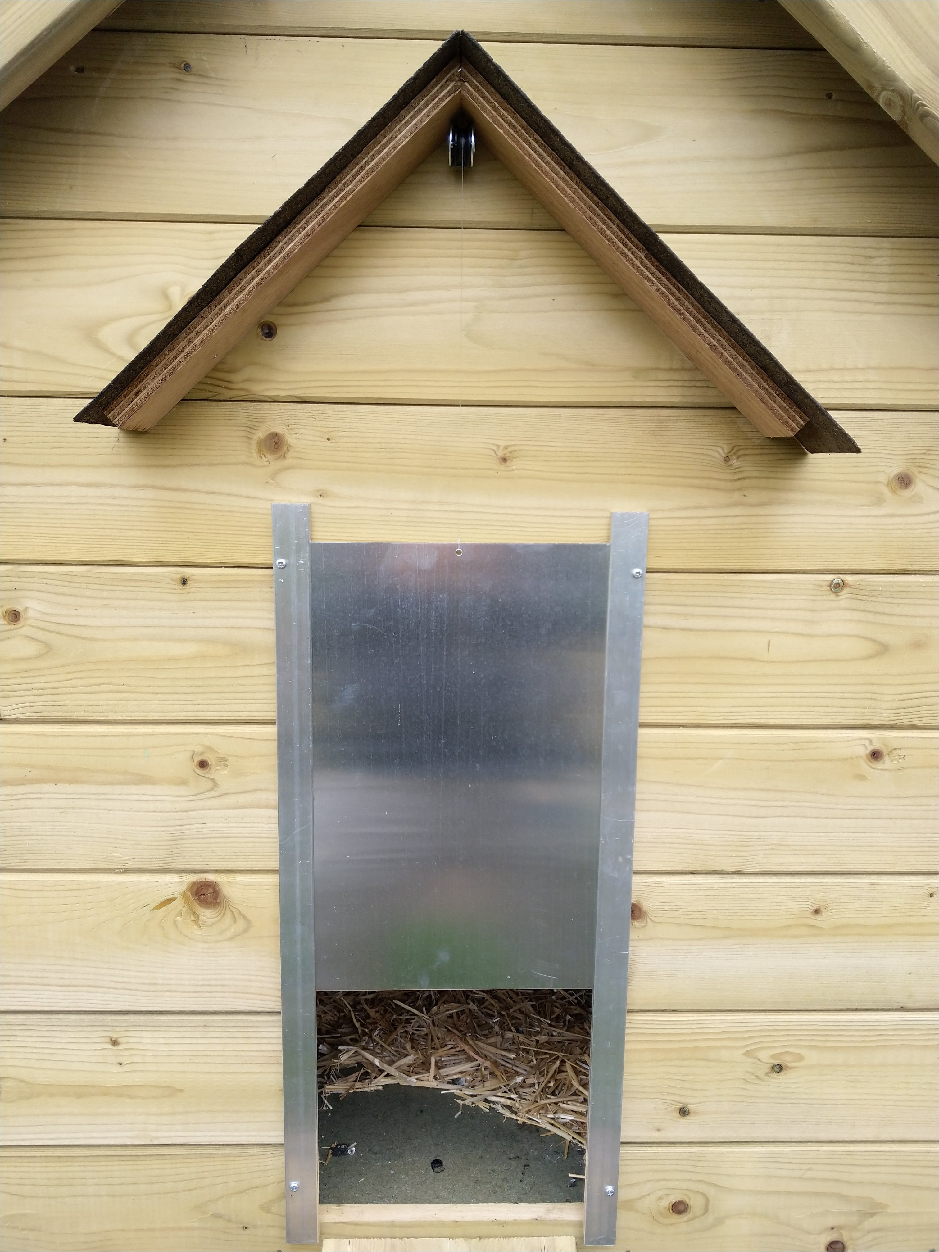 Alu door with pulley to guide nylon wire into the chicken coop. Can you spot the light sensor?