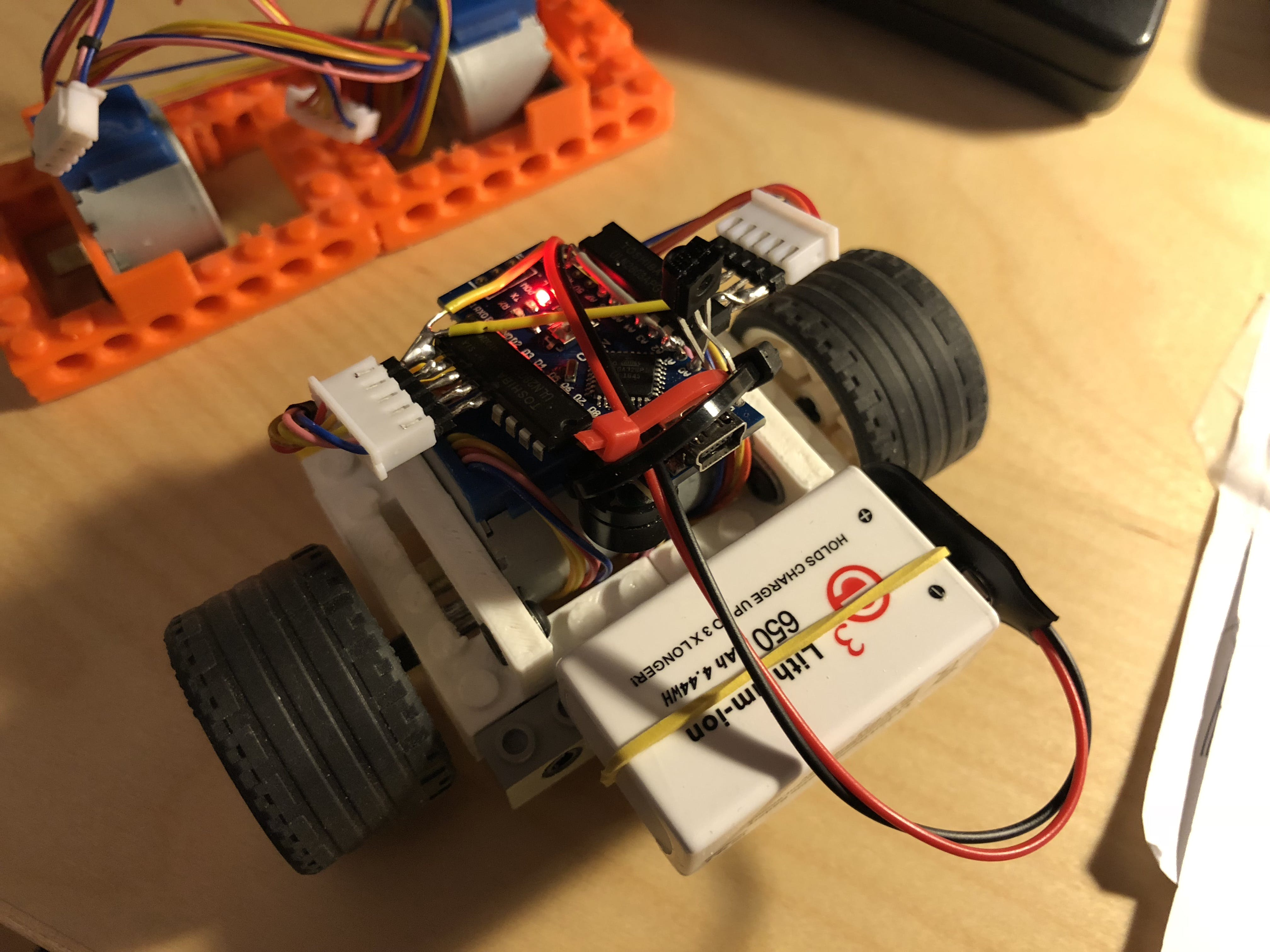 8x8 + wheels and battery sticking out a bit. Parts from bigger bot in the background.