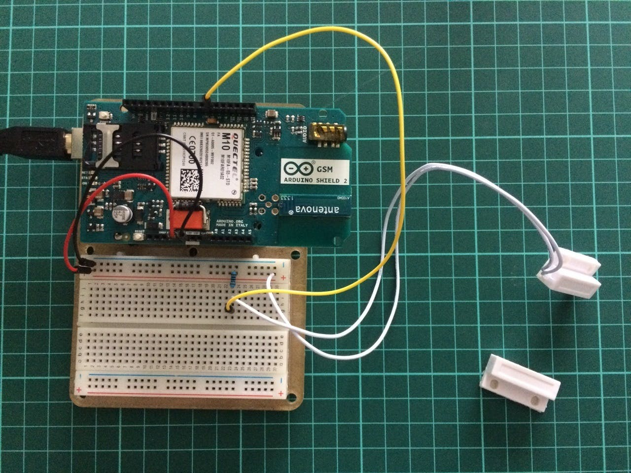 Arduino UNO with GSM shield on to of it and connected reed switch.