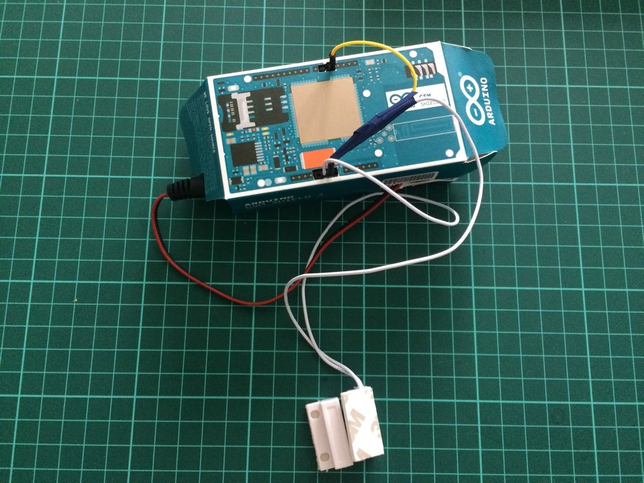 Soldered project packaged into a box from GSM shield with connected 9V battery.