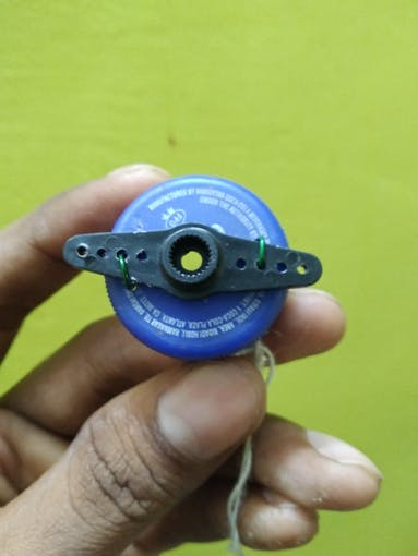 Servo motor shaft connected to bottle cap using copper wires