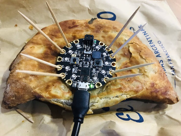 Circuit Playground Express staked down on an empanada with toothpicks