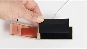 Insert two pieces of velostat between the copper tape.