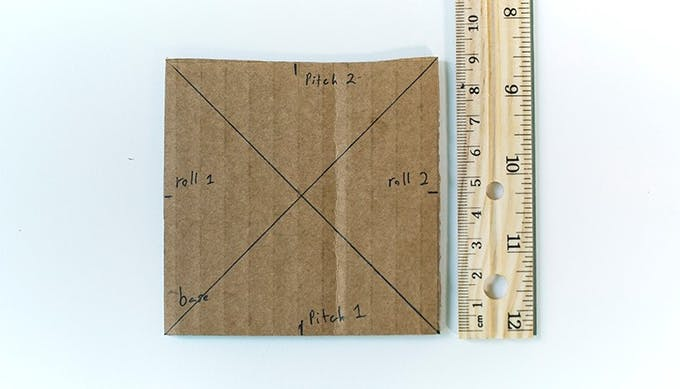 On the Base, measure and mark the halfway point for each side. Label the bottom and top Pitch 1 and Pitch 2, respectively. Label the left and right Roll 1 and Roll 2, respectively.