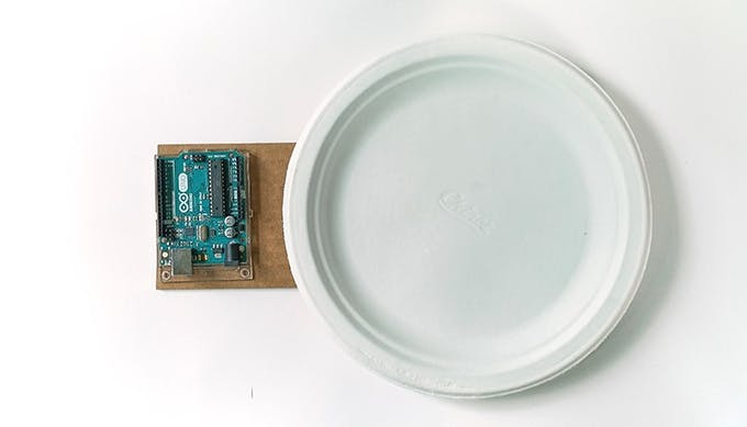On the remaining cardboard piece, glue down your Arduino board and the paper plate.