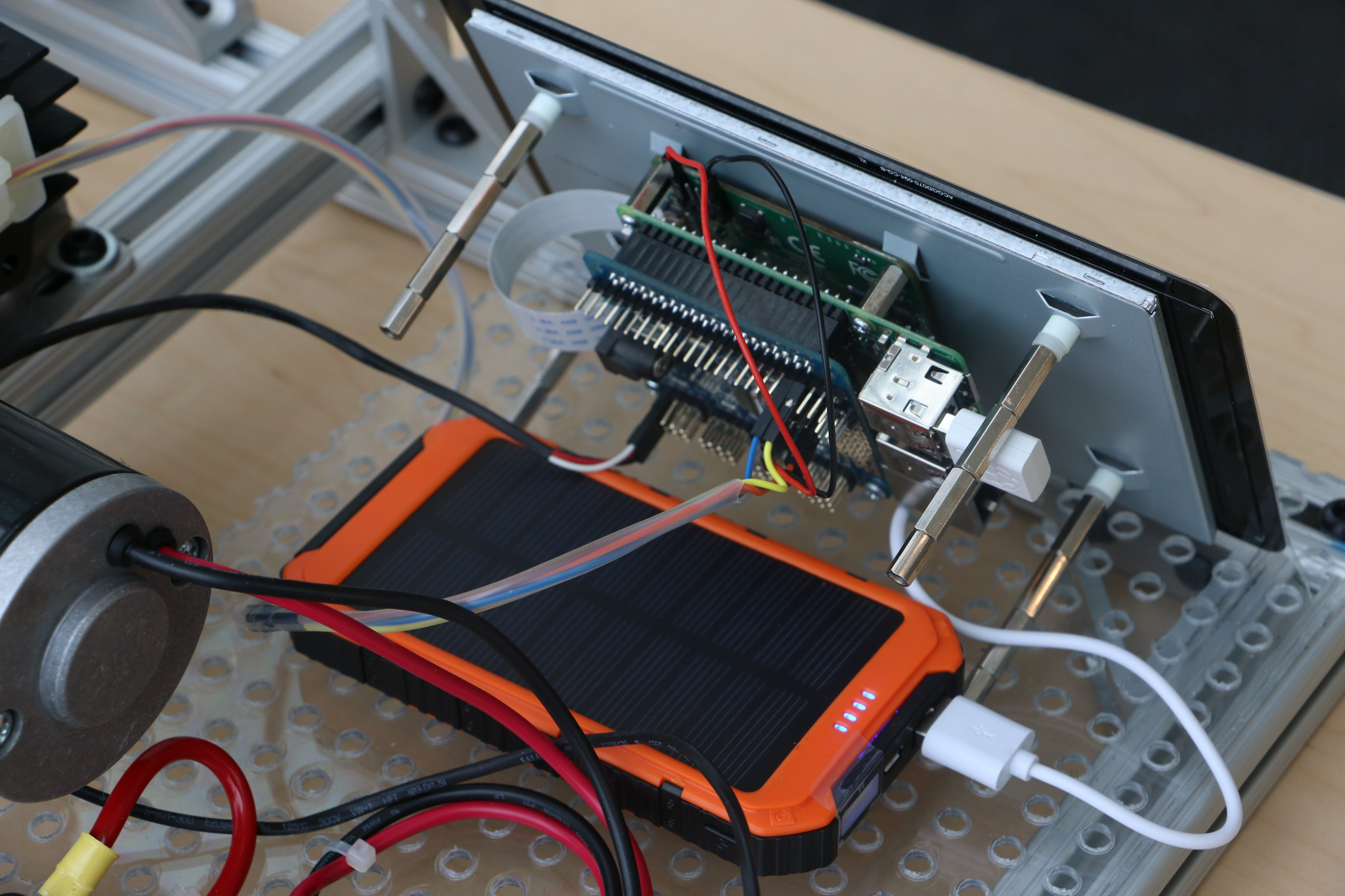 The orange solar powered battery pack powering the RPi3 and Touchscreen