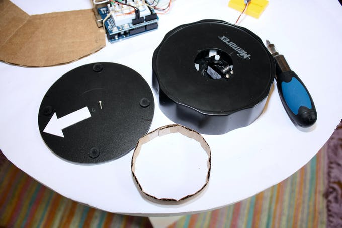 The servo motor is attached to the CD labeler base, and the bottom piece is reused as the surface to sit the camera.  The circular cardboard is added between the two pieces for stability.