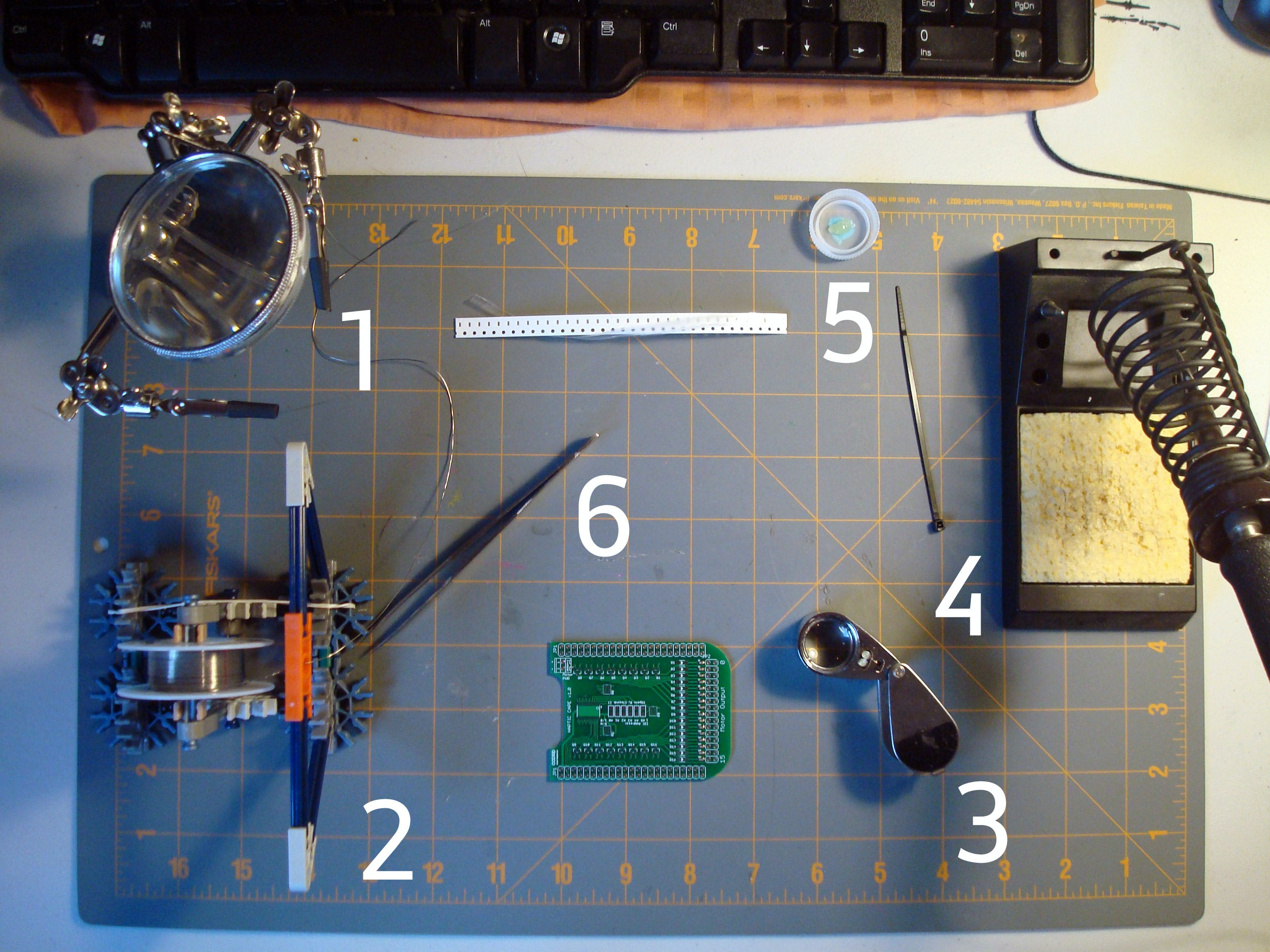 Going counter-clockwise from the upper left. 1: Third hand for holding parts in place. 2: Solder dispenser, made from K'Nex for geek-cred. 3: Jeweler's loupe for close inspection. 4: WES51 Solder Station. 5: A puddle of no-clean flux in a bottlecap with a little plastic stick to move it around. 6: Fine tipped tweezers.