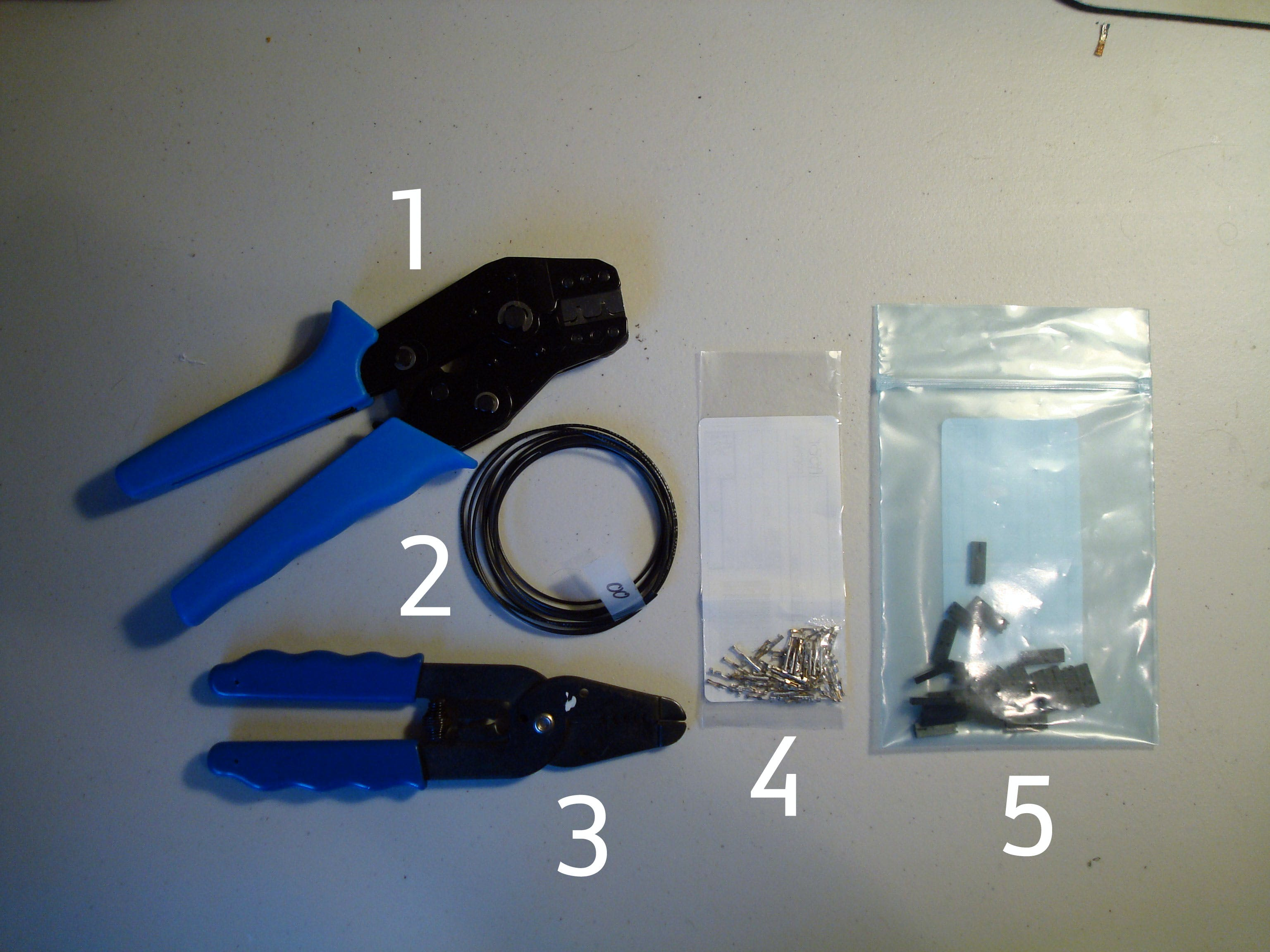 Counter-Clockwise from left. 1: Ratcheting hand crimper. 2: Our cut-wire lengths. 3: wire stripper. 4: The Molex SL female crimp terminals. 5: Molex SL 2 pin crimp housing.