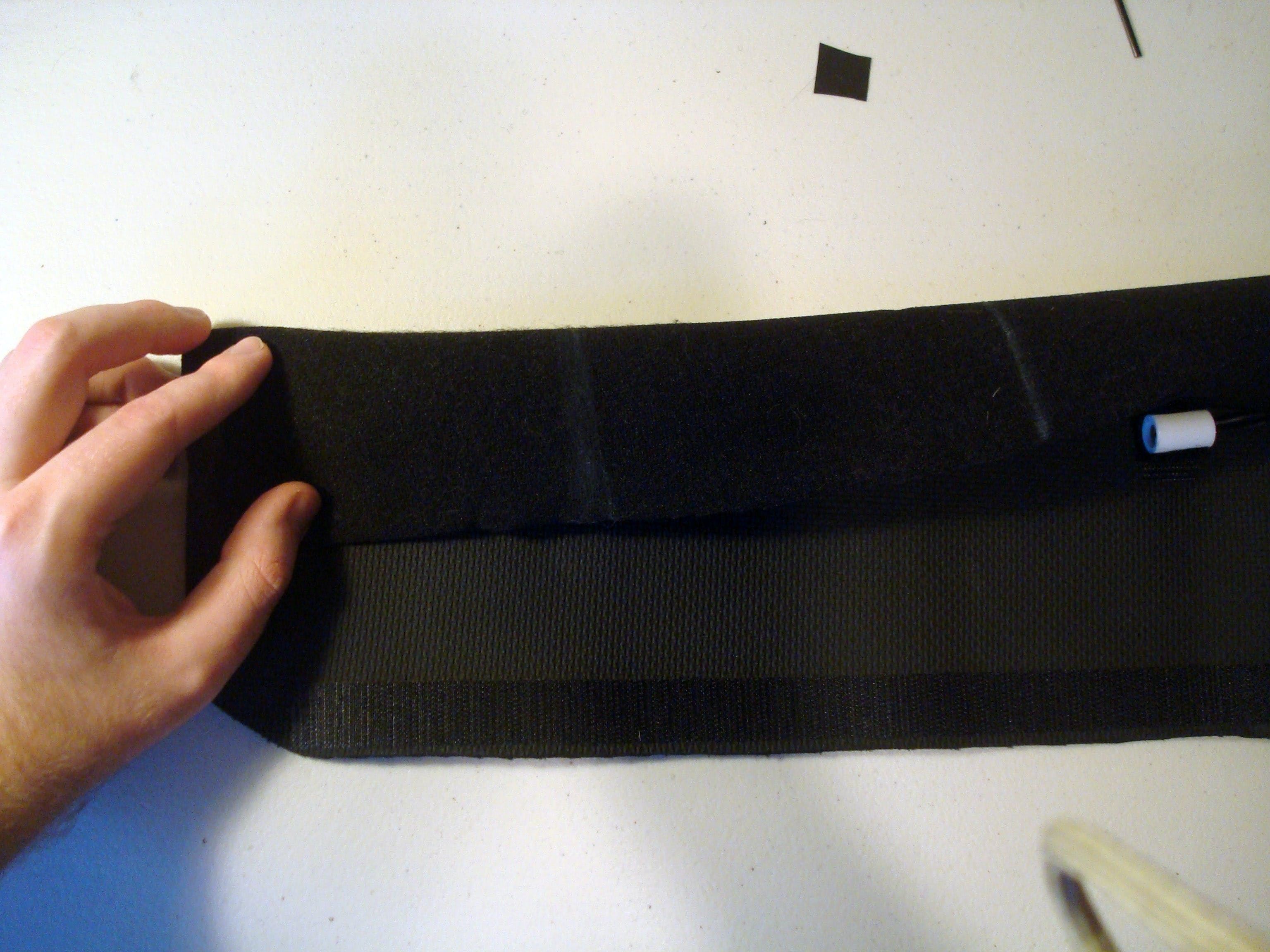 Take the upper edge of the belt (The edge without the velcro on it) and fold it over the tactors.