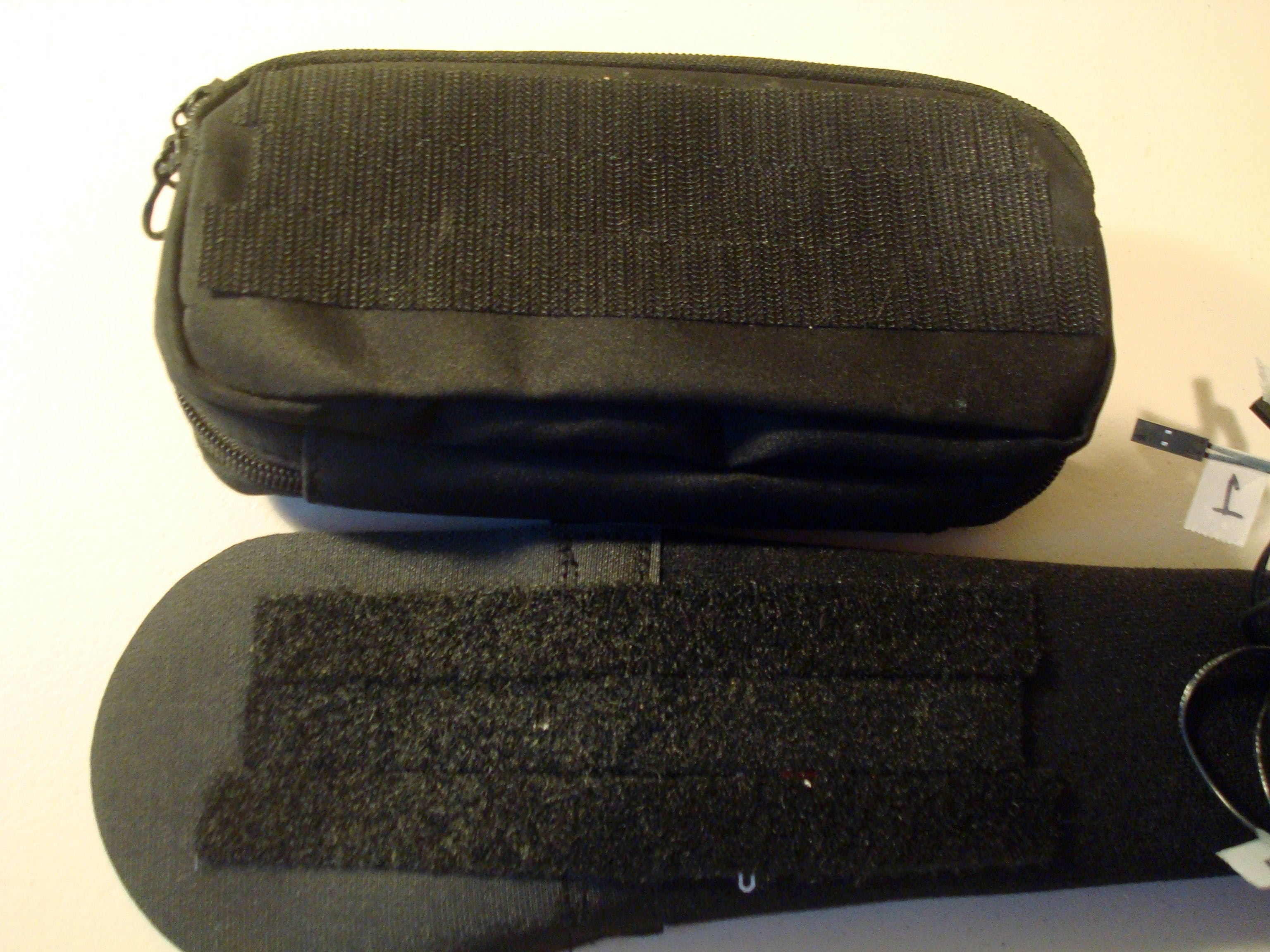 Attach one side of the velcro strips to the back of the case and the other half to the belt, centering the strips across where the belt meets the velcro adjustment strap.