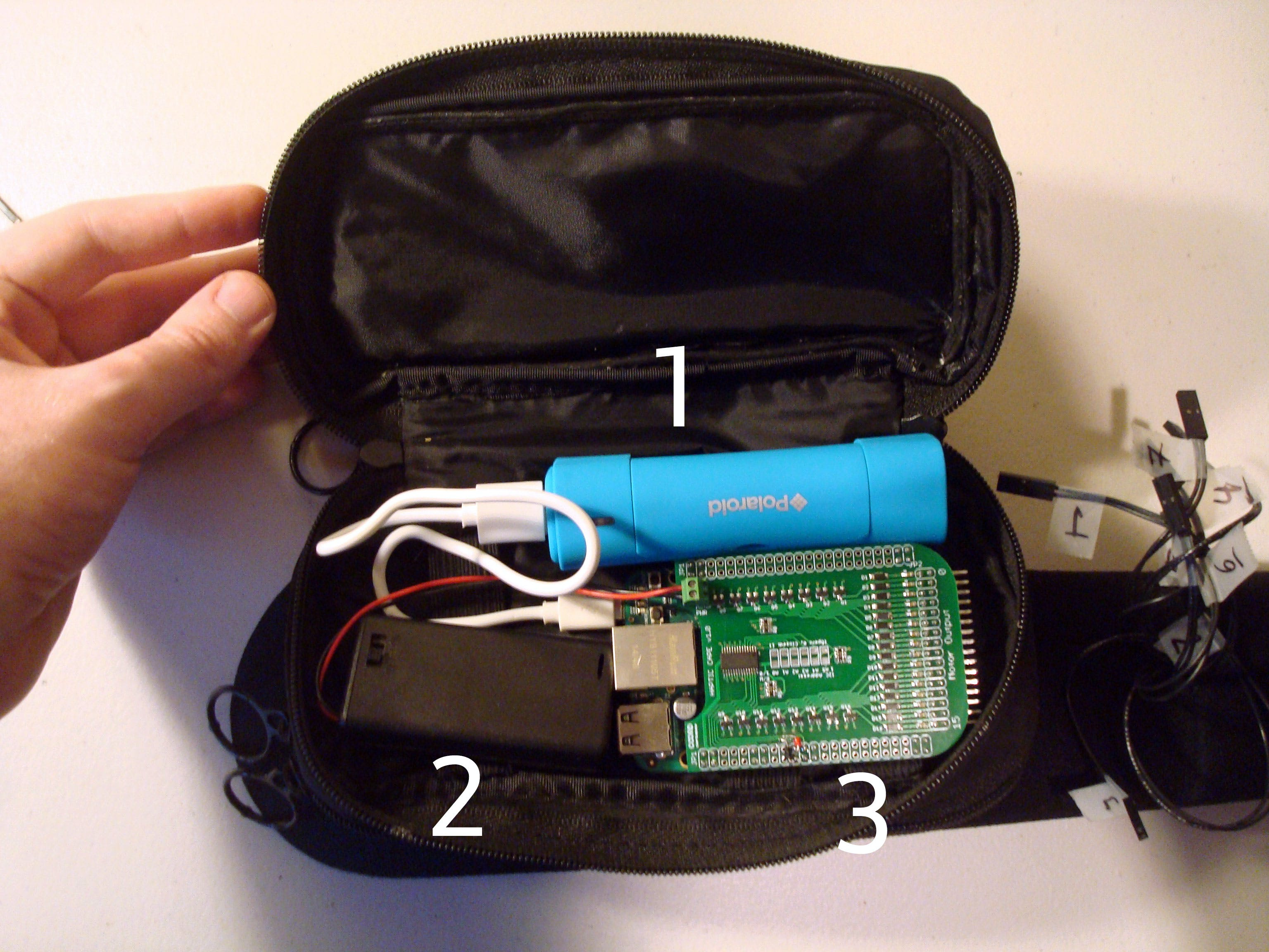 Now that the case and the belt are connected, it's time to load all the parts we need to run the Cape+BeagleBone off the grid. 1: Smartphone battery pack. 2. AA x 2 battery pack to power the tactors. 3: The BeagleBone with Haptic Cape attached.