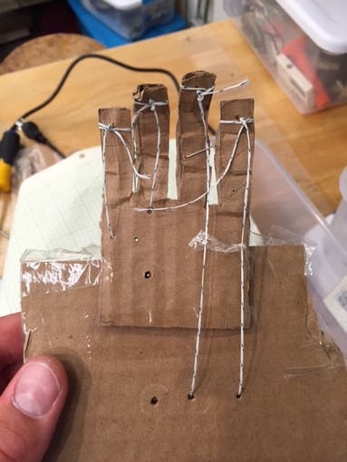 Cardboard prototype with strings that feed into the back connecting to the Servos