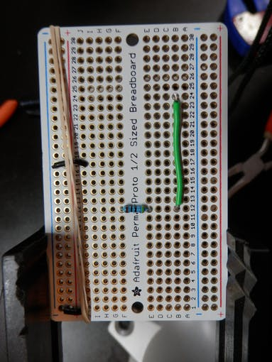 Holding jumper wires with rubber band for soldering