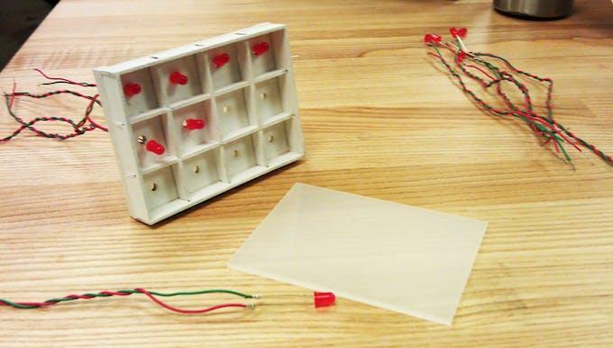 Threading LEDs through the laser cut holes in the plywood box.