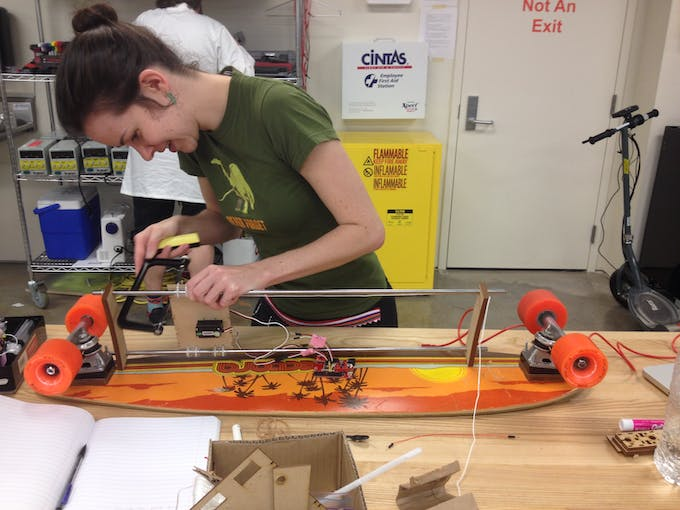 Molly sawing extra notches for rubber bands onto our platform