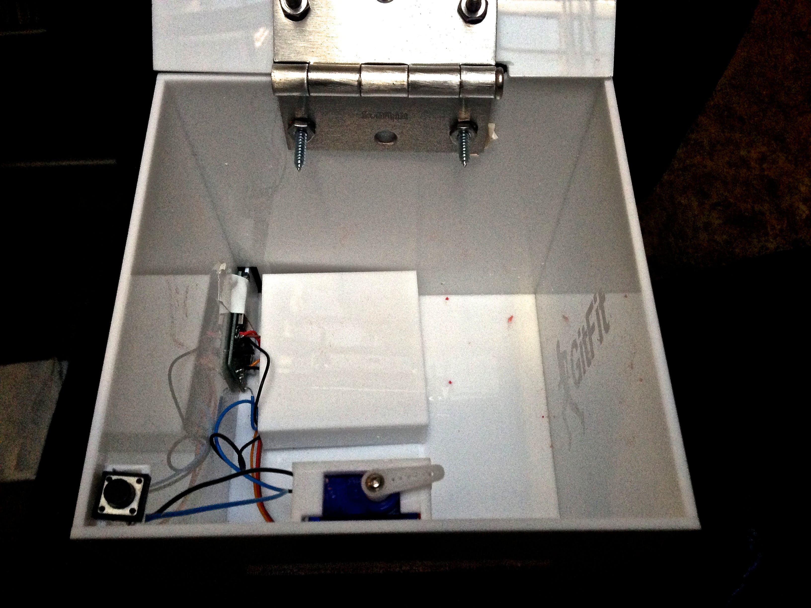 Inside the reward box: battery, electric imp, button switch, and servos motor for locking mechanism