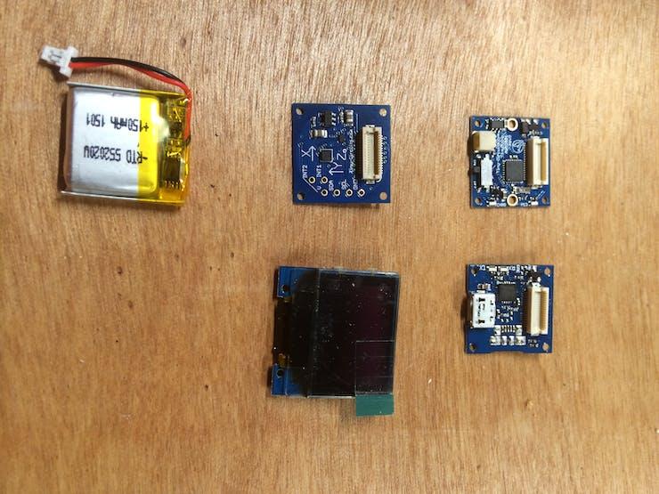 Clockwise from top left: USB TinyShield, TinyScreen, LiPo Battery, Accelerometer TinyShield, TinyDuino LiPo