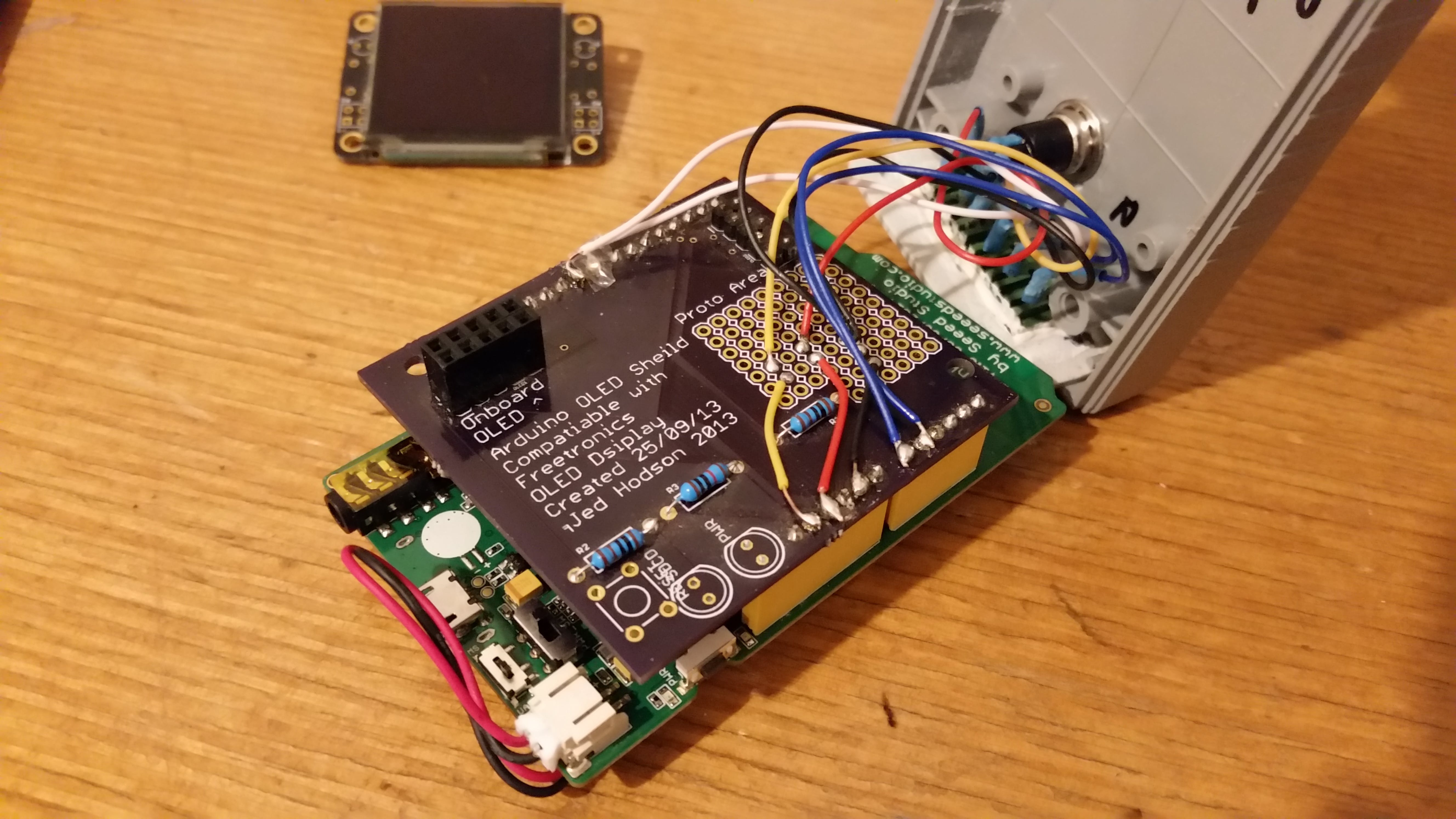 Inside of case - OLED Shield on LinkIt One wired up to terminal block and button