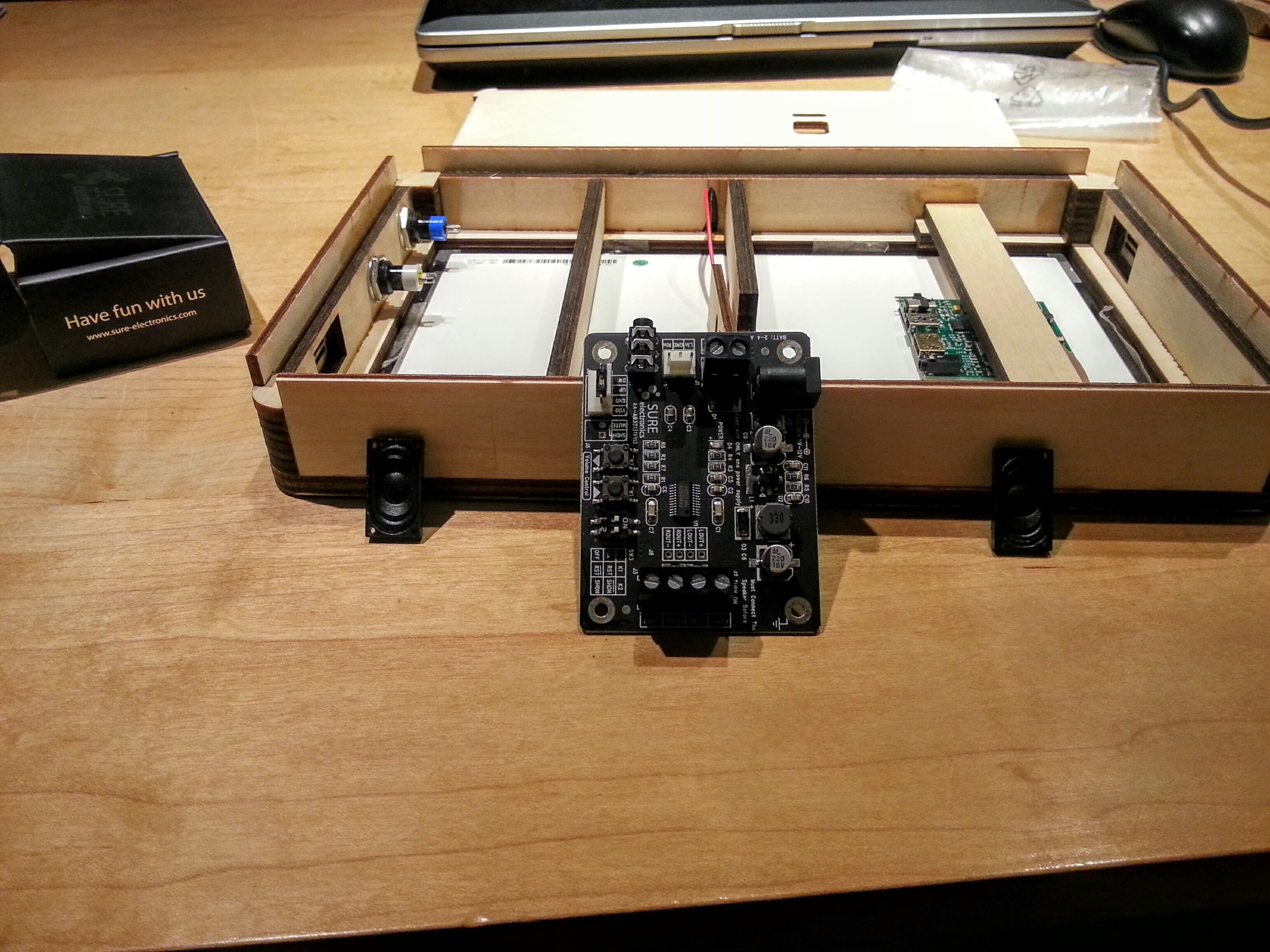 The amp (packaged in a Samsung style) box with the tiny speakers alongside.