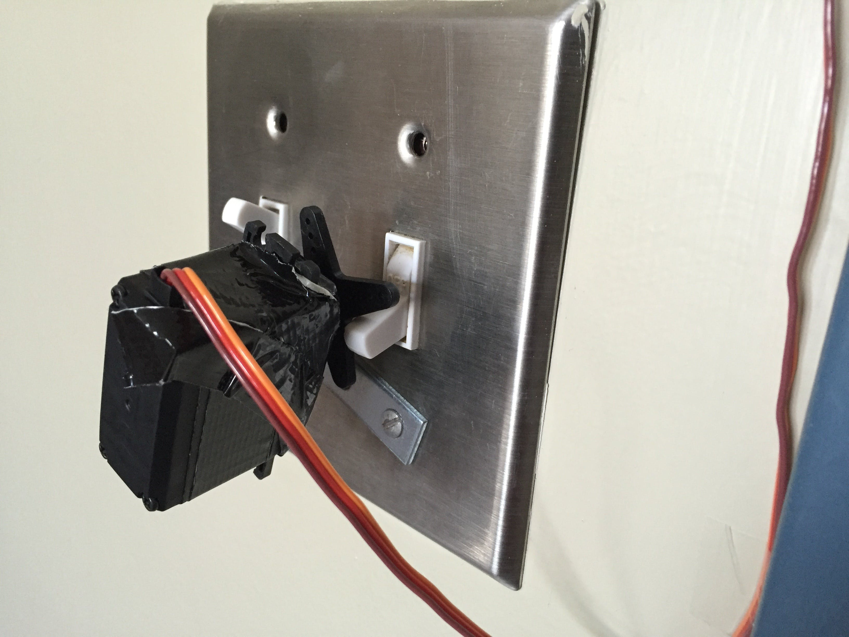The overhead lights in the room are controlled with a simple servo motor attached to the light switch.