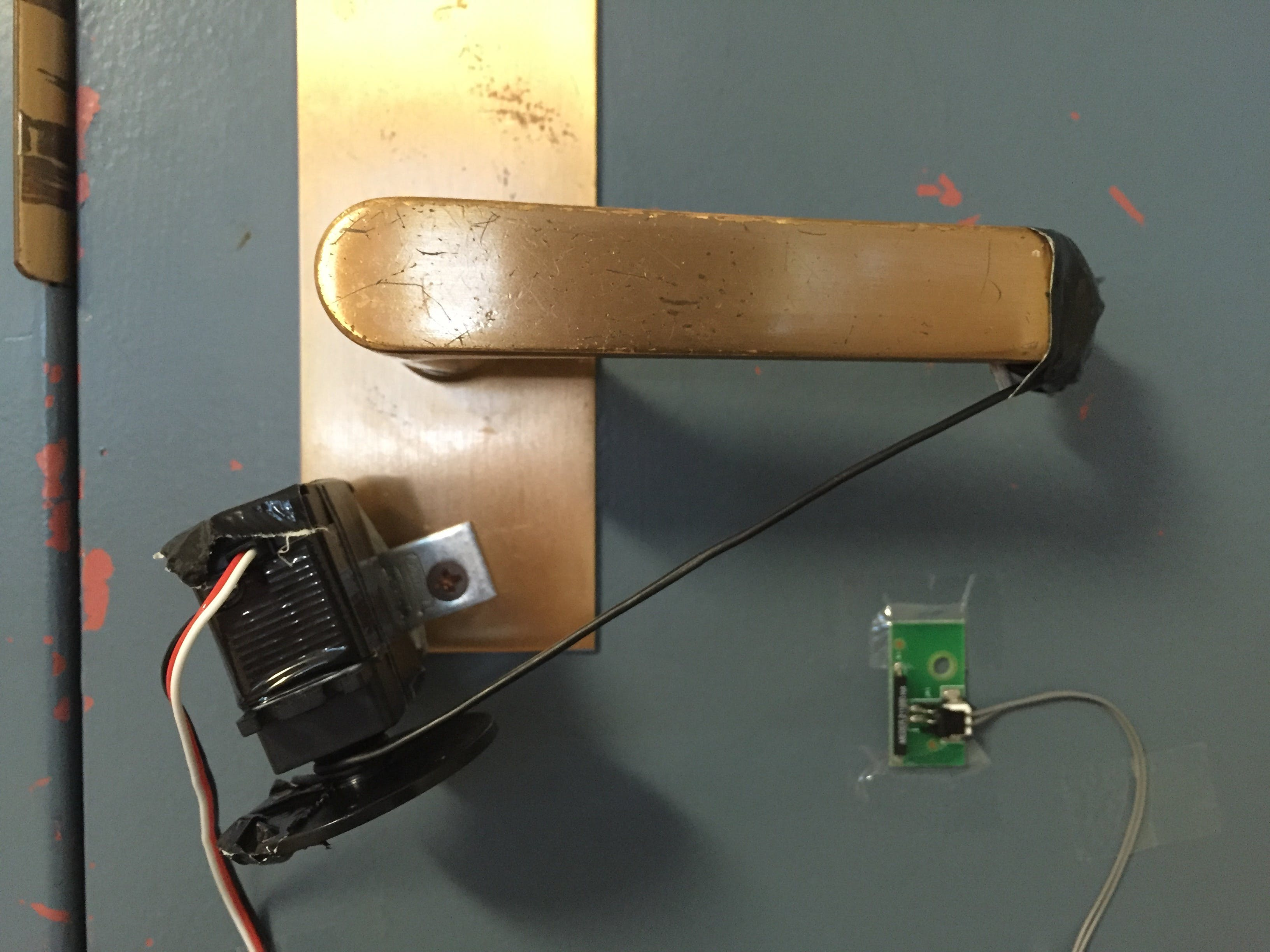 The door lock is controlled by a cable attached between the door handle and a continuous rotation servo. The green PCB in the bottom right of the screen is a Reed switch which detects when the door is unlocked.