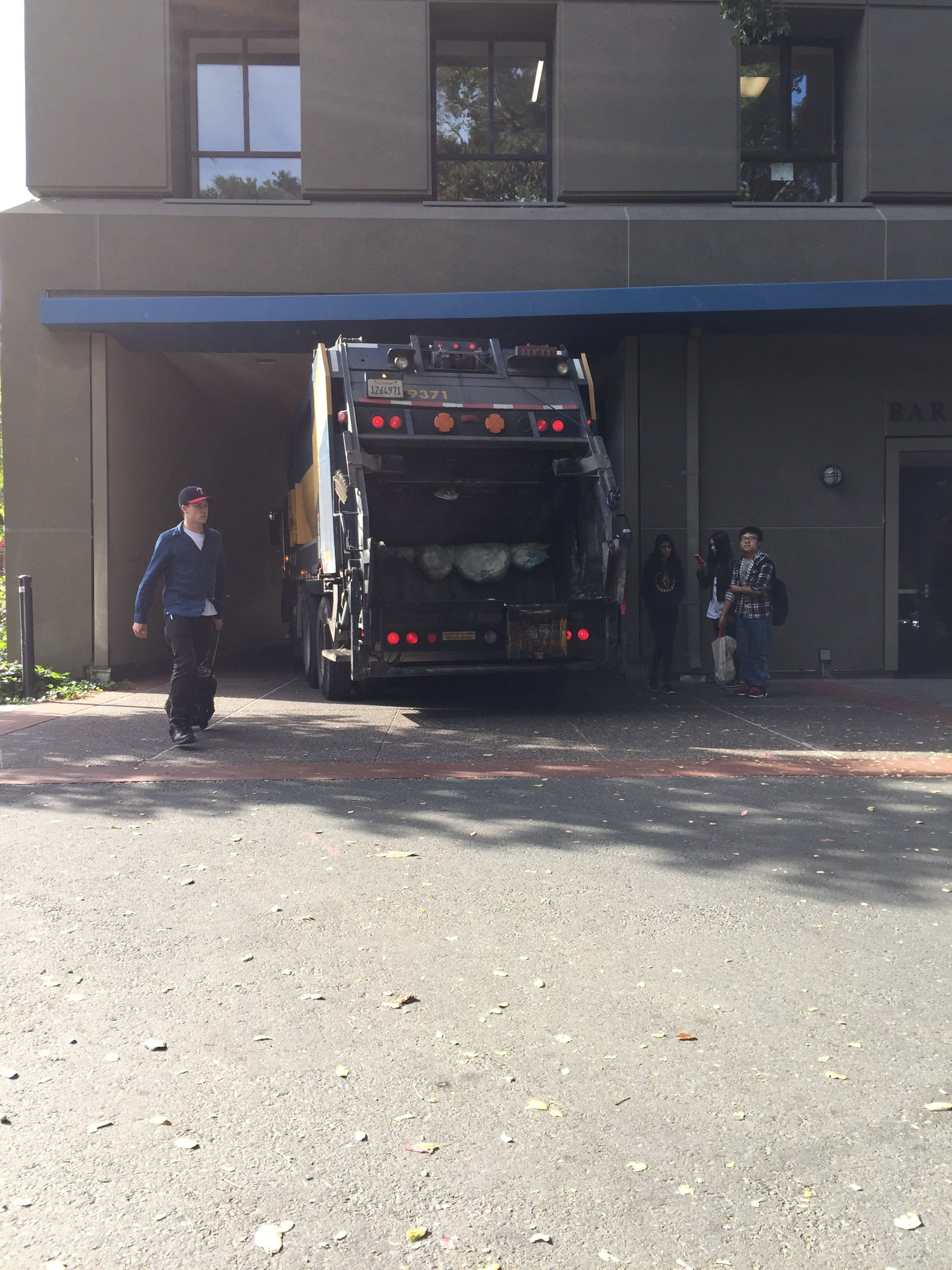 A trash truck passing through the tunnel and pedestrians waiting for it to pass.