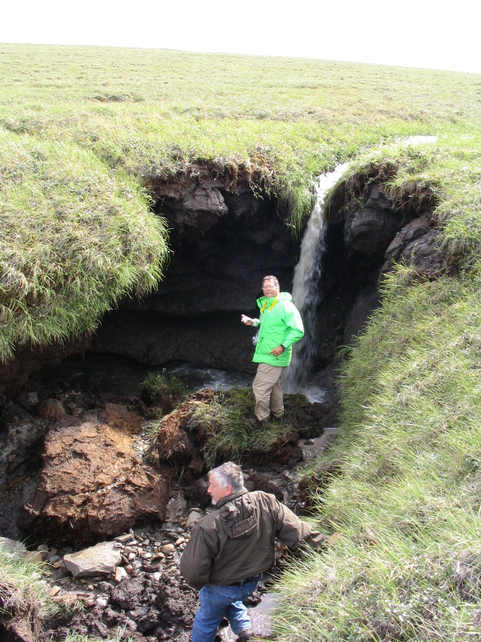 Breck Bowden explores the thermokarst failure on a stream leading into the Toolik River on the day he and Michael Gooseff discovered it in 2003. (Courtesy of Michael Gooseff)